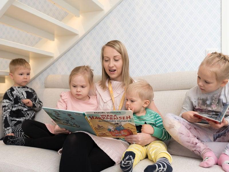 Lastenhoito: Sohvalla lukemassa