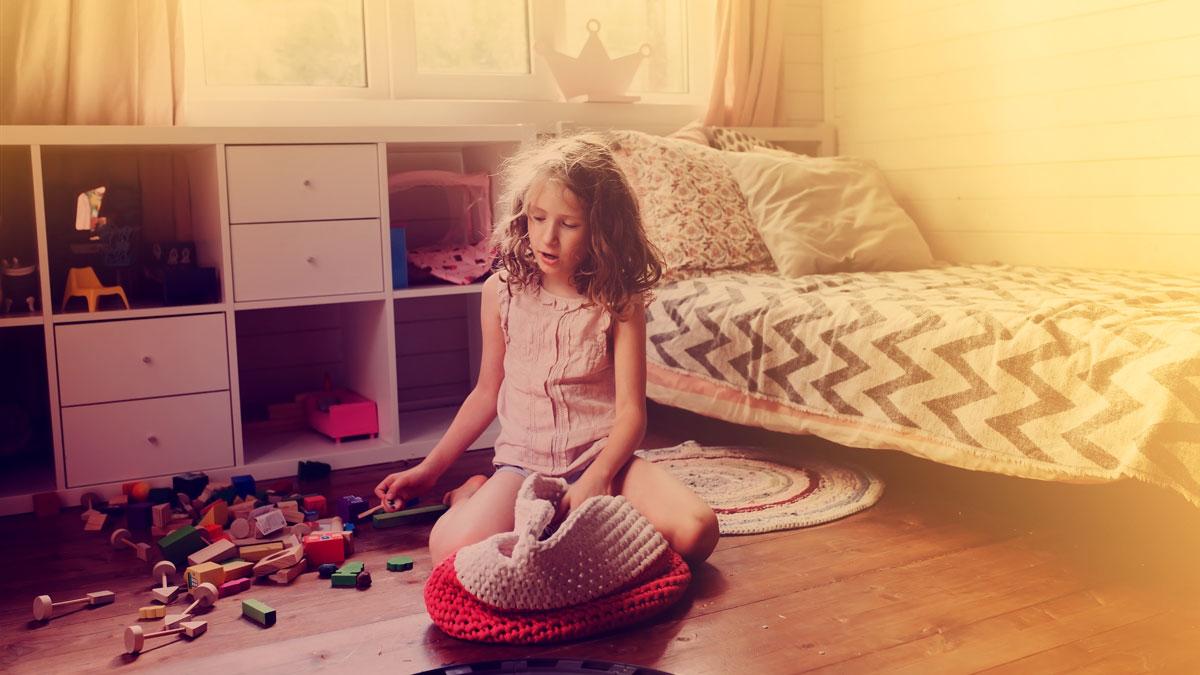 Lapsi siivoaa leluja lattialta